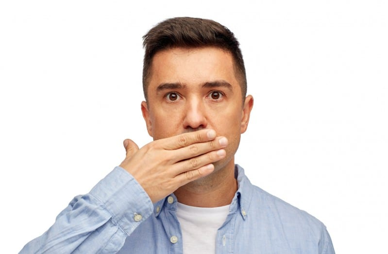 man covers his mouth with hand