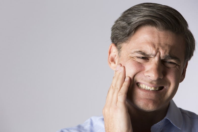 Man with jaw pain presses his hand against his face