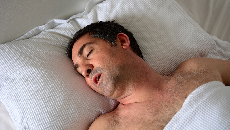 Man with mouth wide open snores in bed