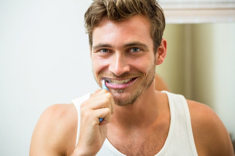 Man standing in front of his bathroom mirror brushing his teeth