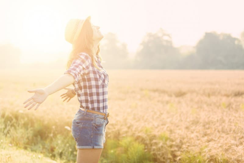 Young woman with outstretched arms looks up to the sunny sky while walking in a field