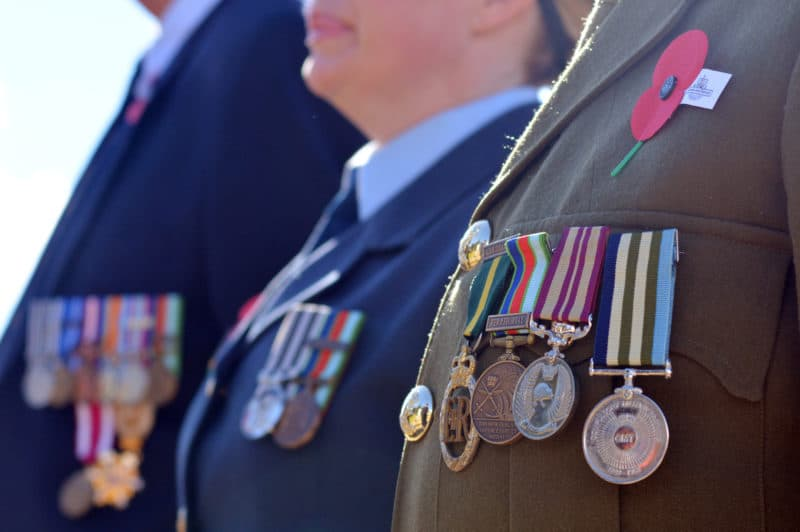 Military personnel standing at attention with metals on their jackets