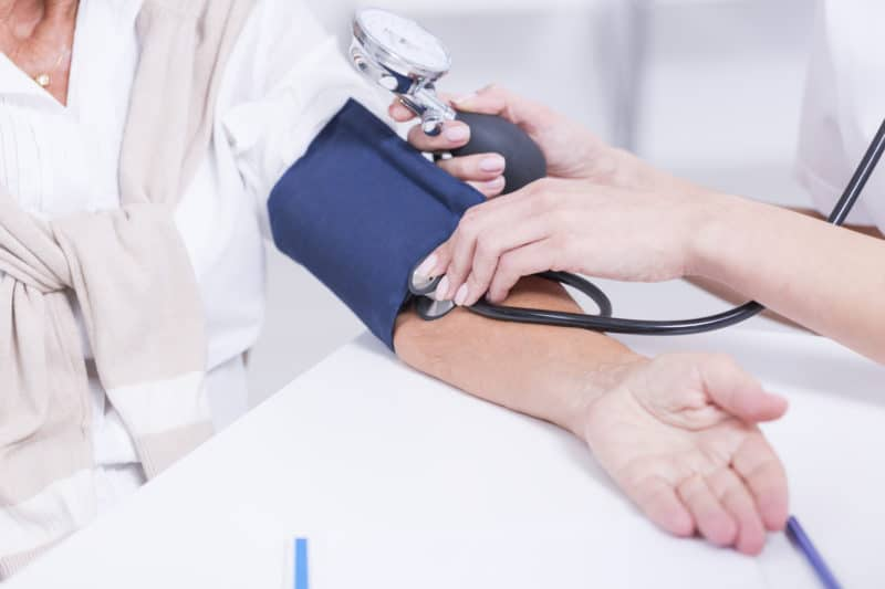female taking blood pressure of a patient