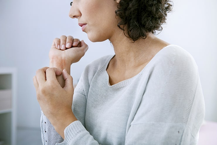 Woman itching arm. Psoriasis and Gum Disease may be linked