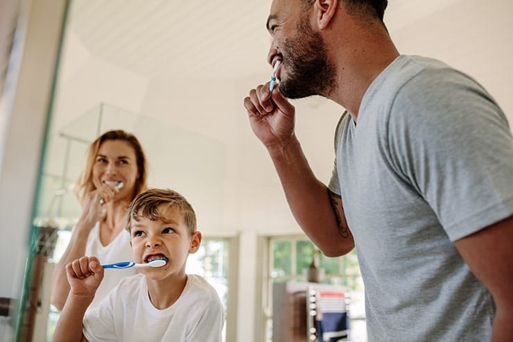 A young family spends the time brushing their teeth together to promote good oral hygiene. The amount of fluoride in your toothpaste comes into question as does it better prevent cavities or not.