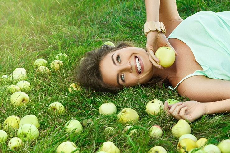 An attractive young woman laying under an apple tree. Those apples has a very destint fruity smell, just like the how you breath might smell when on the Keto diet.