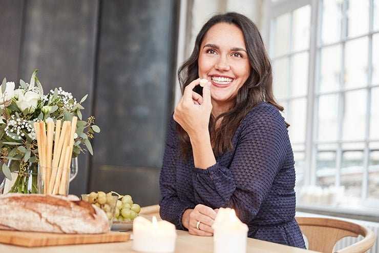 Attractive woman sitting at the kitchen table, eating and laughing. It's amazing how a dental implant has dramatically changed her smile!