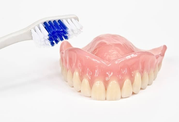 An upper denture sitting on a countertop with a toothbrush. Now that you have a new set of dentures it's time to have a daily care schedule.