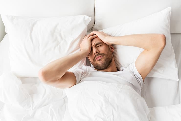 Young man waking with with a headache. For those who wake up with headaches, it can be difficult to get off on the right foot in the morning. If you tend to experience early morning headaches, there could be a few possible reasons why.