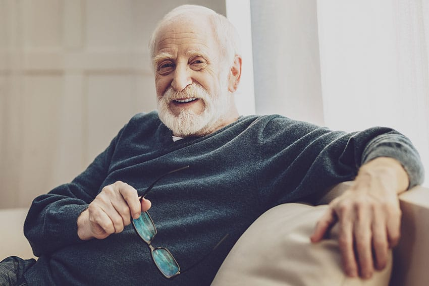 older man relaxing on his couch at home