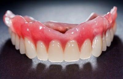 A close up of dentures with a dark background.