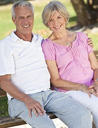 Happy, older couple sitting on a park bench